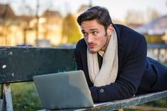 Uomo d'affari elegante bello che lavora in un parco Immagine Stock Libera da Diritti