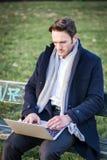 Uomo d'affari elegante bello che lavora in un parco Fotografia Stock Libera da Diritti