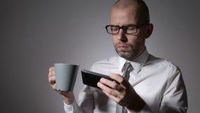 Uomo d'affari elegante in camicia bianca che tiene una tazza di caffè o un tè in mani L'uomo ha fatto una rottura sul lavoro, fac archivi video