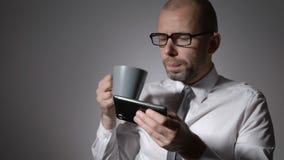 Uomo d'affari elegante in camicia bianca che tiene una tazza di caffè o un tè in mani L'uomo ha fatto una rottura sul lavoro, fac stock footage