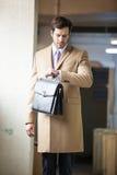 Uomo d'affari elegante che esamina il suo orologio fotografie stock