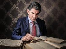 Uomo d'affari elegante che legge alcuni libri Immagine Stock