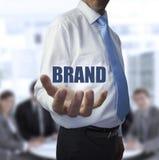 Uomo d'affari elegante che tiene la marca di parola Immagini Stock