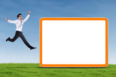 Uomo d'affari emozionante che salta con il bordo in bianco Immagine Stock