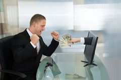 Uomo d'affari emozionante con soldi che escono dallo schermo di computer Fotografie Stock
