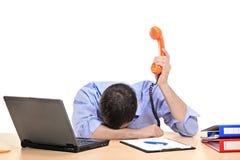 Uomo d'affari esaurito che tiene un tubo del telefono Fotografia Stock Libera da Diritti