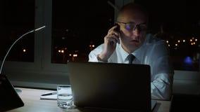 Uomo d'affari esecutivo che parla con telefono che si siede alla tavola in ufficio scuro alla notte archivi video