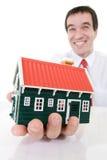 Uomo d'affari estatico con una casa miniatura Immagine Stock