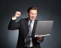 Uomo d'affari estatico ed entusiasta con il computer portatile - buone notizie, c Fotografia Stock