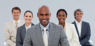 Uomo d'affari etnico con suo sorridere della squadra Immagini Stock