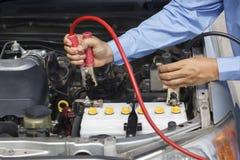 Uomo d'affari facendo uso dei cavi di saltatore per avviare un'automobile Fotografia Stock Libera da Diritti