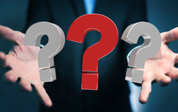 Uomo d'affari facendo uso dei punti interrogativi della rappresentazione 3D Immagini Stock