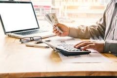Uomo d'affari facendo uso dei soldi della tenuta e del calcolatore fotografia stock libera da diritti
