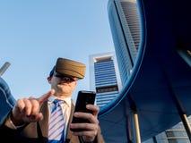 Uomo d'affari facendo uso dei vetri di realtà virtuale con un telefono cellulare dentro Fotografie Stock