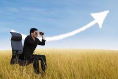 Uomo d'affari facendo uso del binocolo che esamina la nuvola crescente del grafico Fotografie Stock