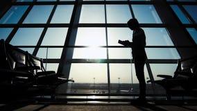 Uomo d'affari facendo uso del computer della compressa all'aeroporto siluetta di un viaggiatore dell'uomo con lo zaino Affare e v video d archivio