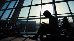 Uomo d'affari facendo uso del computer della compressa all'aeroporto siluetta di un viaggiatore dell'uomo con lo zaino Affare e v archivi video
