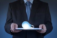 Uomo d'affari facendo uso del computer della compressa che coltiva lampadina Immagine Stock Libera da Diritti
