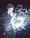 Uomo d'affari facendo uso del computer portatile con i grafici Fotografia Stock