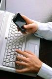 Uomo d'affari facendo uso del computer portatile e del telefono cellulare Fotografia Stock