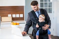 Uomo d'affari facendo uso del computer portatile mentre portando neonata Fotografia Stock