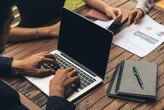 Uomo d'affari facendo uso del computer portatile nella riunione d'affari Fotografie Stock