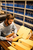 Uomo d'affari facendo uso del computer portatile sulla tavola nel magazzino dell'archivio Fotografia Stock