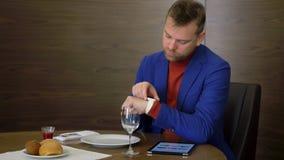 Uomo d'affari facendo uso del pc della compressa per la rete sociale di lettura rapida mentre aspettando l'alimento di ordine stock footage