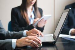 Uomo d'affari facendo uso del suo computer portatile nel corso di una riunione immagine stock libera da diritti