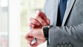 Uomo d'affari facendo uso del suo orologio astuto video d archivio