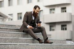 Uomo d'affari facendo uso del telefono cellulare app che manda un sms fuori dell'ufficio in città urbana con le costruzioni dei g fotografia stock libera da diritti