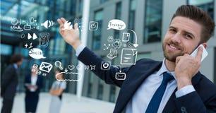 Uomo d'affari facendo uso del telefono cellulare dalle icone che rappresentano multi incarico fotografie stock