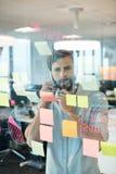 Uomo d'affari facendo uso del telefono cellulare mentre esaminare l'adesivo nota i grafici su vetro Fotografia Stock