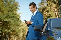 Uomo d'affari facendo uso del telefono vicino la sua automobile Immagini Stock