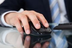 Uomo d'affari facendo uso del topo del computer allo scrittorio Fotografie Stock Libere da Diritti