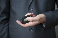 Uomo d'affari facendo uso della chiave dell'automobile Immagini Stock