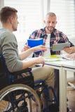 Uomo d'affari facendo uso della compressa digitale con il collega di handicap immagini stock libere da diritti