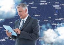 Uomo d'affari facendo uso della compressa digitale contro i termini di affari in cielo Immagini Stock Libere da Diritti