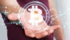 Uomo d'affari facendo uso della rappresentazione di cryptocurrency 3D dei bitcoins Immagine Stock Libera da Diritti