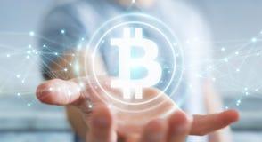 Uomo d'affari facendo uso della rappresentazione di cryptocurrency 3D dei bitcoins Immagine Stock