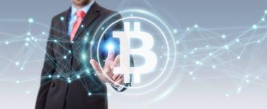 Uomo d'affari facendo uso della rappresentazione di cryptocurrency 3D dei bitcoins Fotografia Stock Libera da Diritti