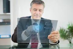 Uomo d'affari facendo uso dello schermo attivabile al tatto futuristico per osservare i dati Fotografie Stock