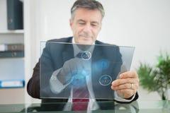 Uomo d'affari facendo uso dello schermo attivabile al tatto futuristico per osservare le statistiche Fotografie Stock