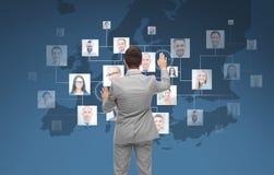 Uomo d'affari facendo uso dello schermo virtuale con i contatti Fotografia Stock Libera da Diritti