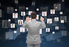 Uomo d'affari facendo uso dello schermo virtuale con i contatti Fotografia Stock