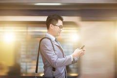 Uomo d'affari facendo uso dello smartphone alla stazione della metropolitana Fotografie Stock Libere da Diritti
