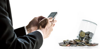 Uomo d'affari facendo uso dello smartphone, con le monete con il contenitore, su fondo bianco Immagine Stock