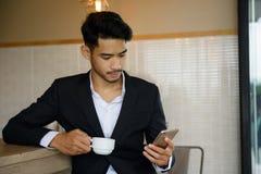 Uomo d'affari facendo uso dello smartphone durante il tempo del caffè Immagine Stock