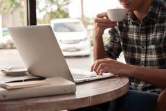 Uomo d'affari facendo uso dello smartphone e del computer portatile che beve una tazza di caffè Fotografia Stock