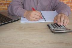 Uomo d'affari facendo uso di un calcolatore per calcolare i numeri Contabilità, contabilità, concetto di calcolo Immagini Stock